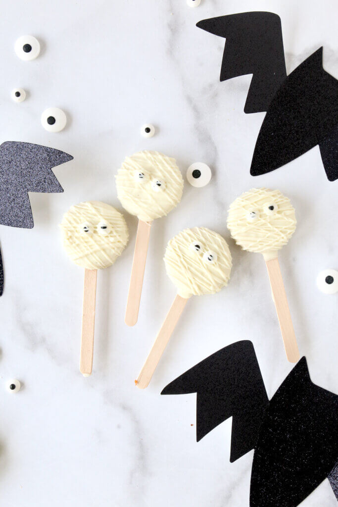 Four oreo cookies dipped in white chocolate with eyeballs.