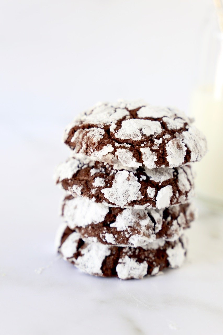 a stack of four chocolate cookies next to a glass of milk