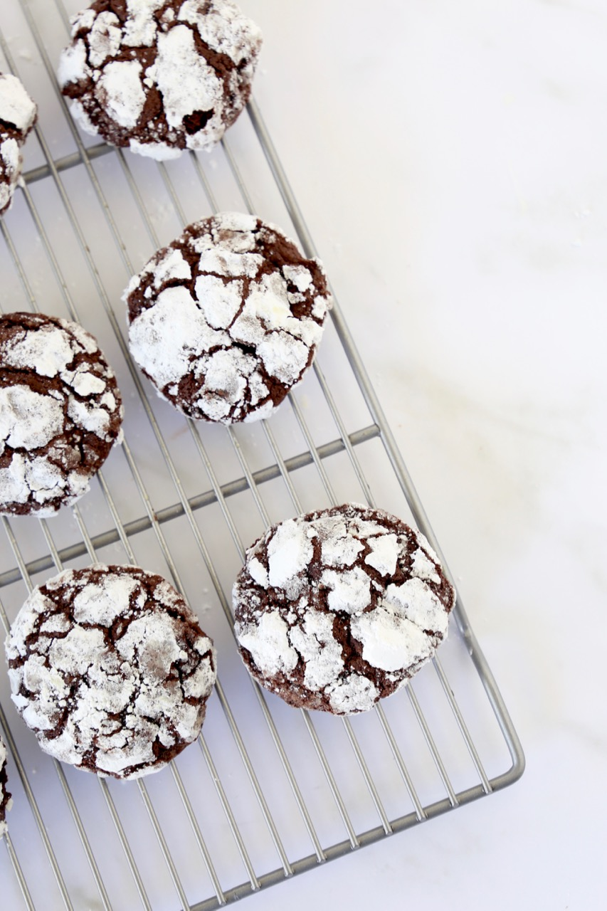 a cooling rack with chocolate crackle cookies lined up to cool off