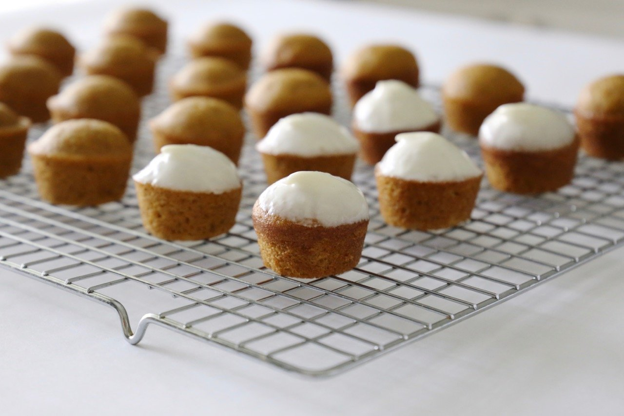 A close up of mini pumpkin spice muffins with cream cheese glaze on top