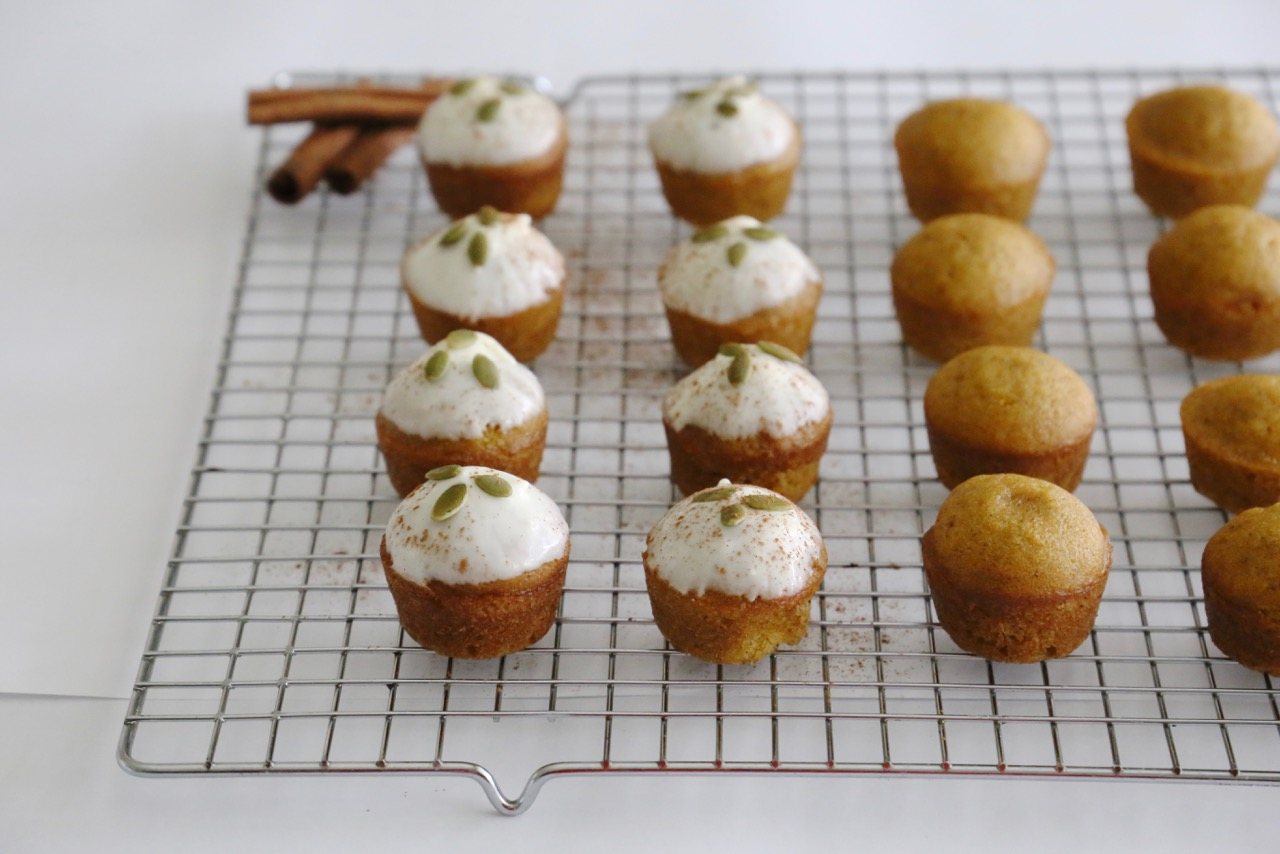 12 mini pumpkin spice muffins on a cooling rack, half of them topped with cream cheese glaze and pumpkin seeds