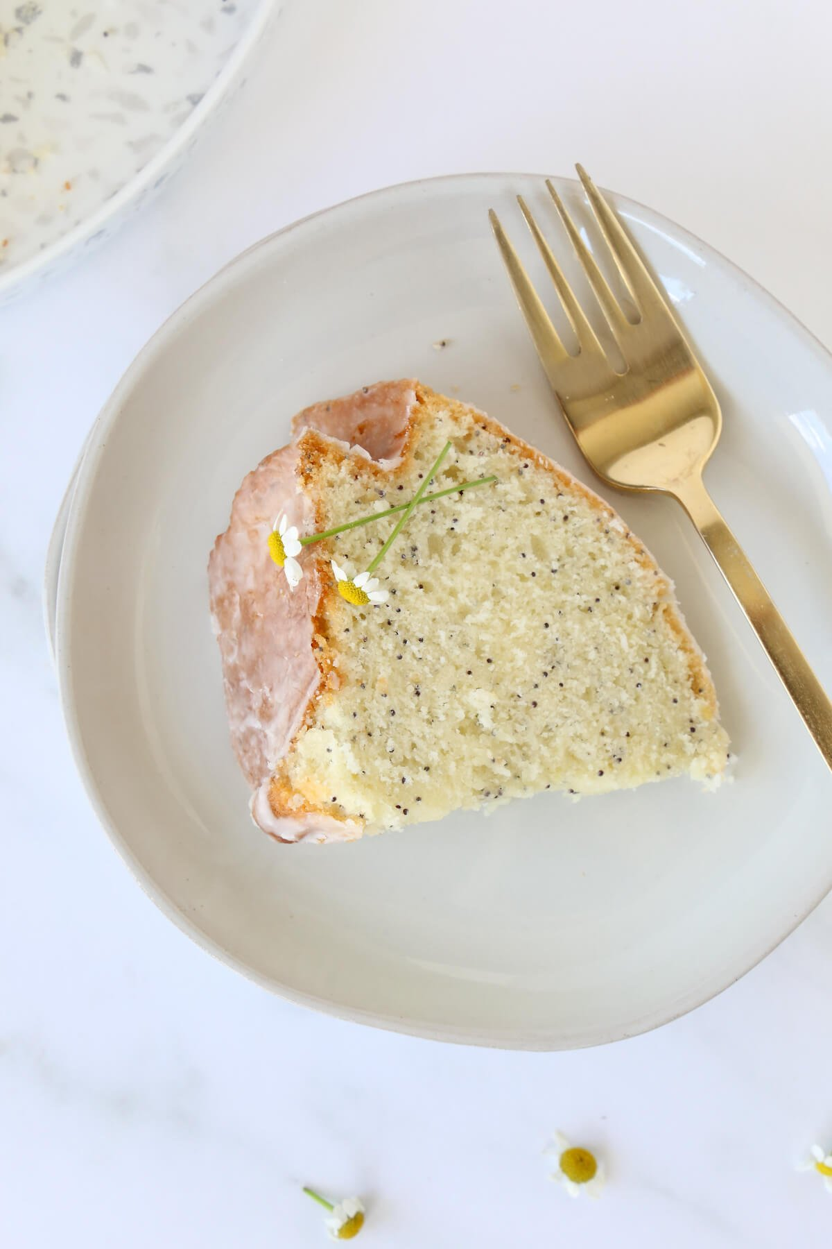 A Slice of lemon cake on a plate with a gold fork.