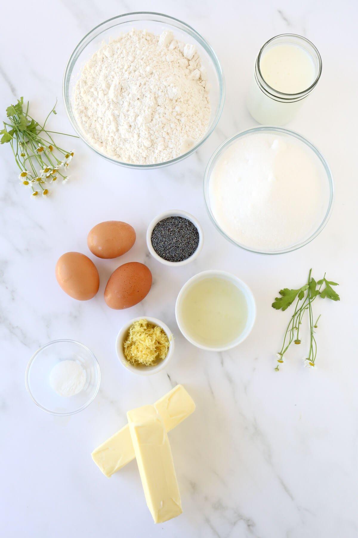 Bowls of flour, sugar, poppy seeds, lemon juice, lemon zest, eggs and butter.