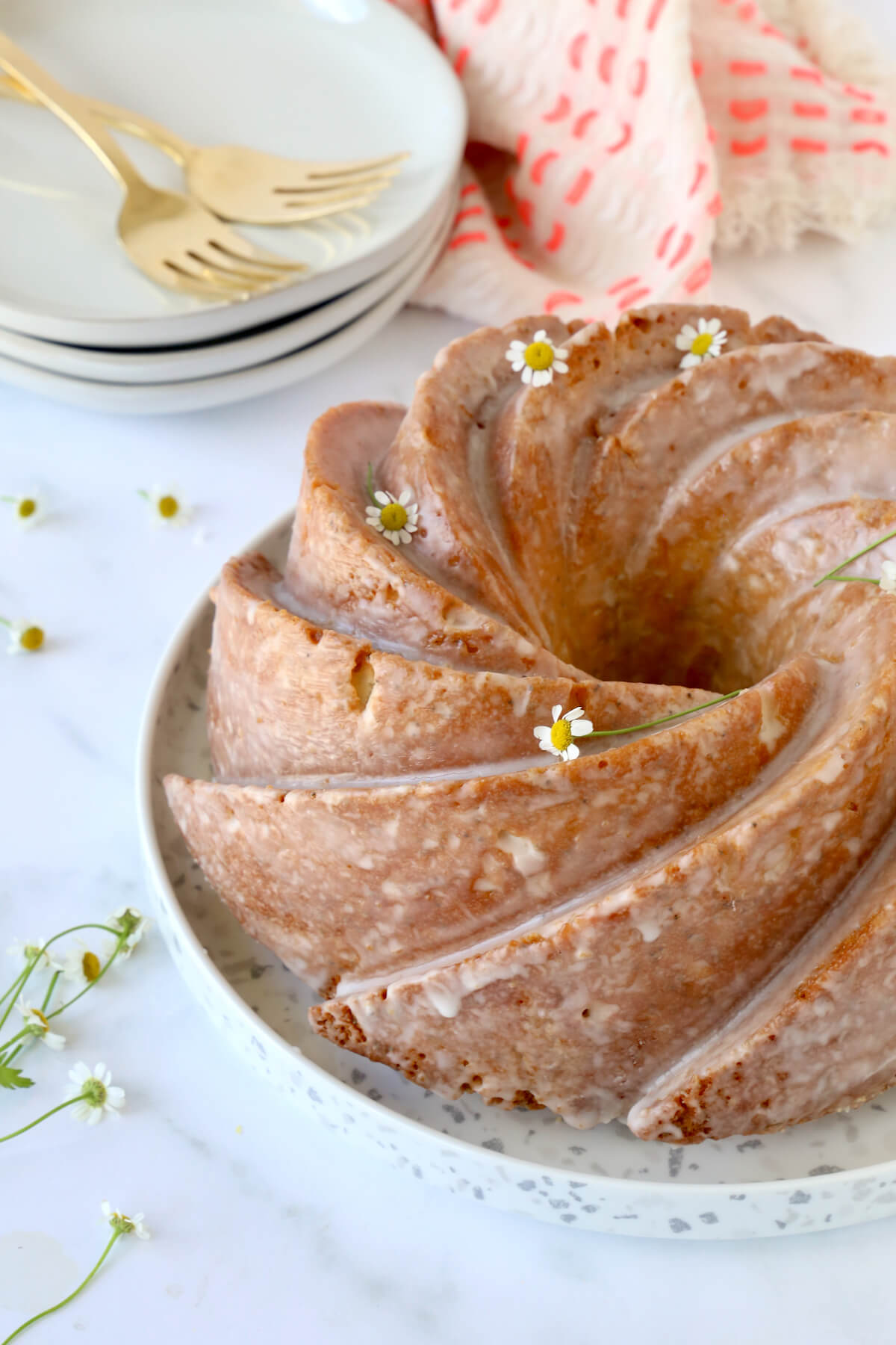 A nine inch bundt cake on a plate next to a stack of three dessert dishes and forks.