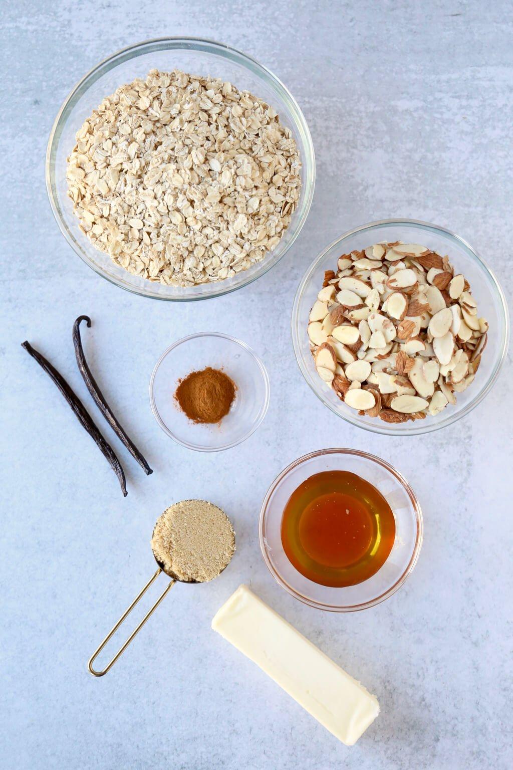 a bowl of oats, almonds, cinnamon, honey, brown sugar, butter and vanilla bean to make granola