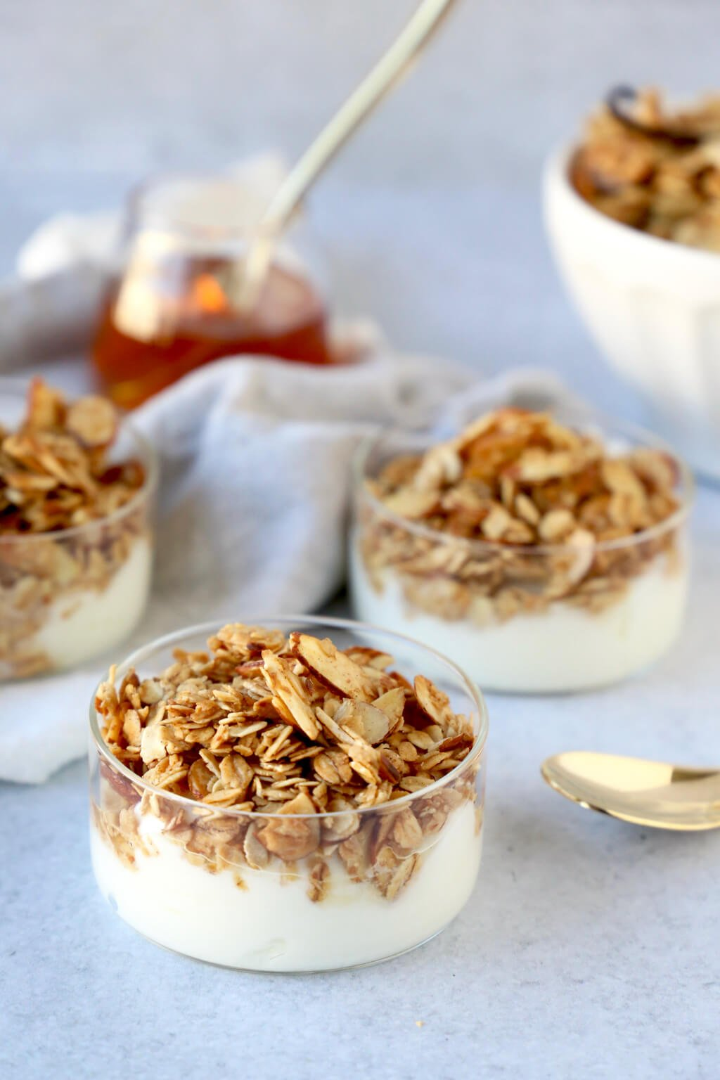 Three bowls of yogurt parfait topped with granola and honey