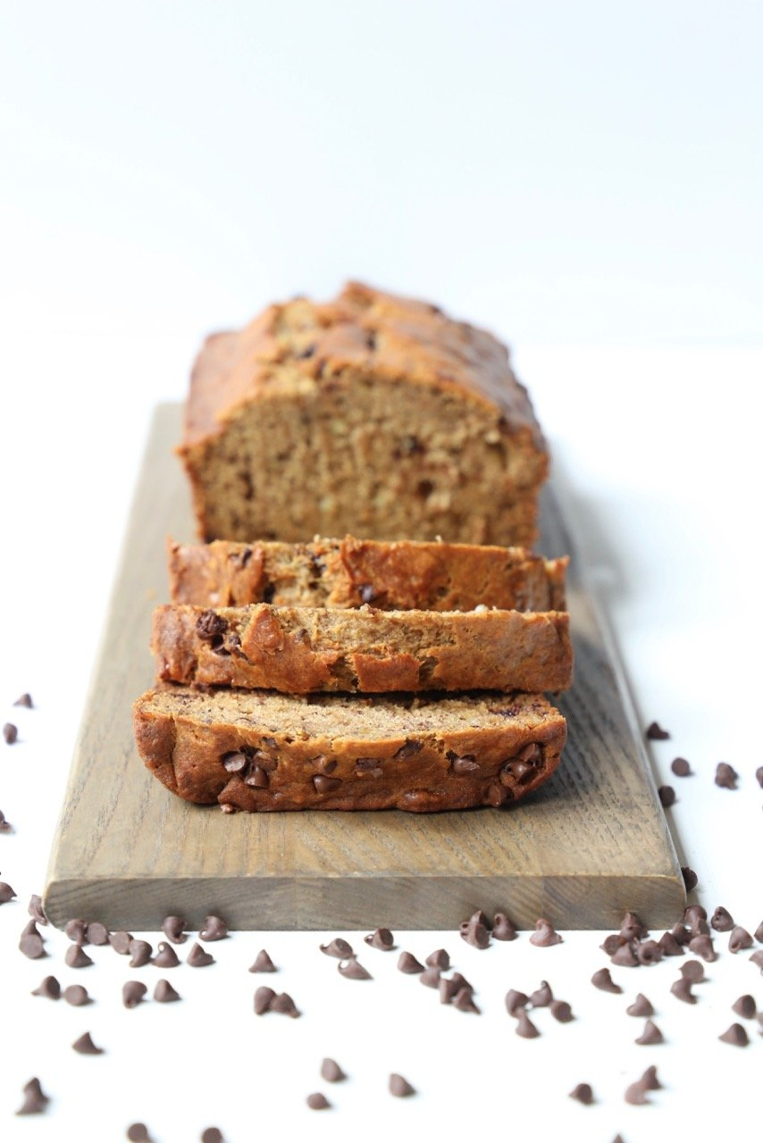 a loaf of banana bread sliced on a wood board with chocolate chips sprinkled around it