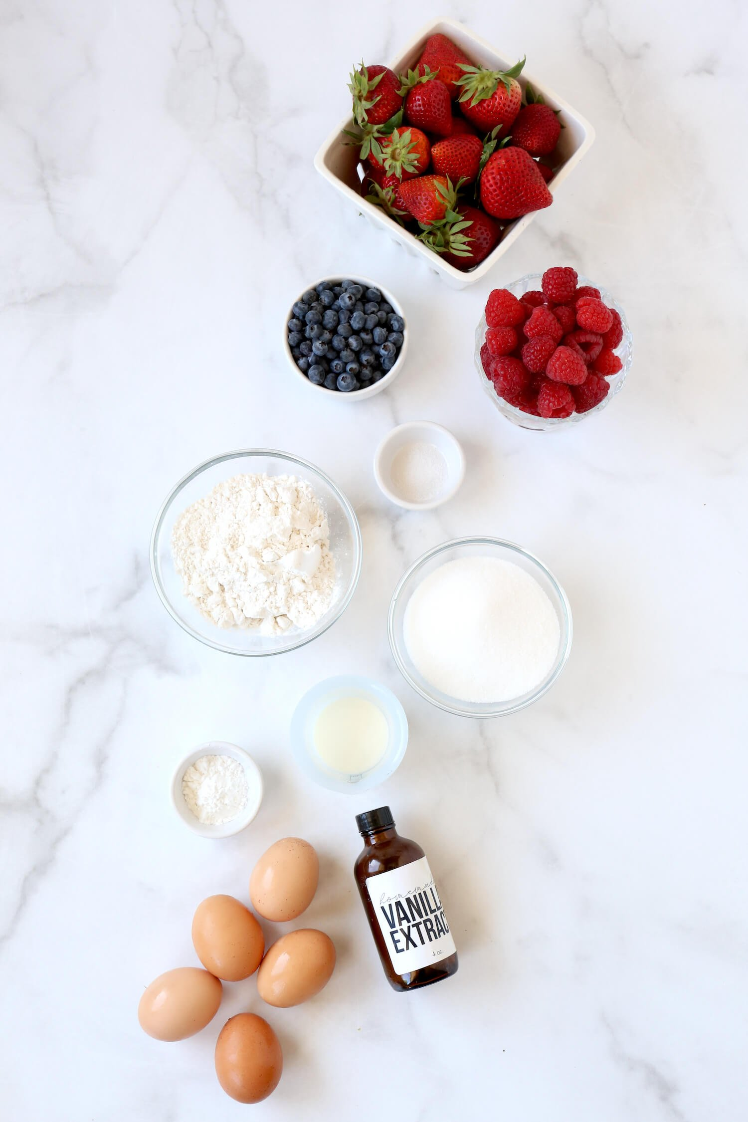Bowls of strawberries, raspberries, blueberries, flour, sugar, vanilla extract, salt and eggs.