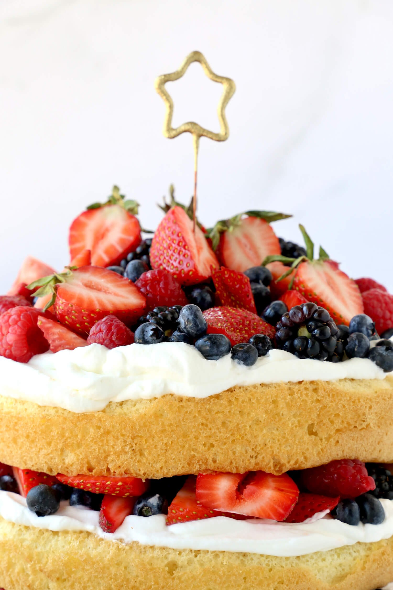 A layer of sponge cake with fresh whipped cream and berries and a star candle.