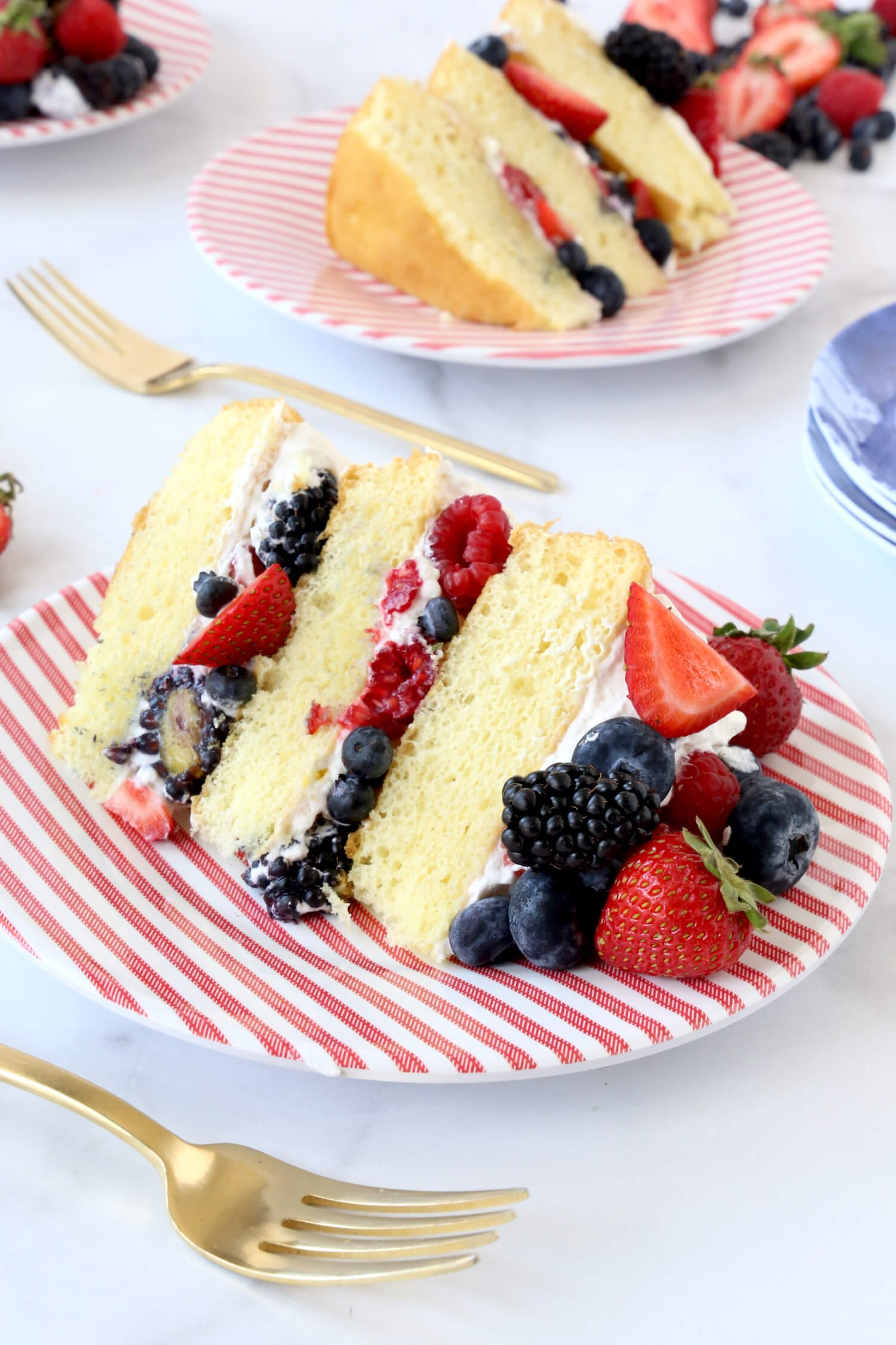 A slice of cake on a red and white stripe plate.