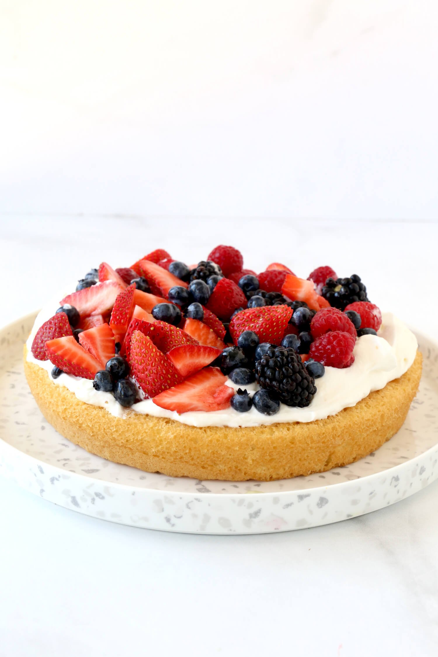 A layer of sponge cake with whipped cream and fresh fruit.
