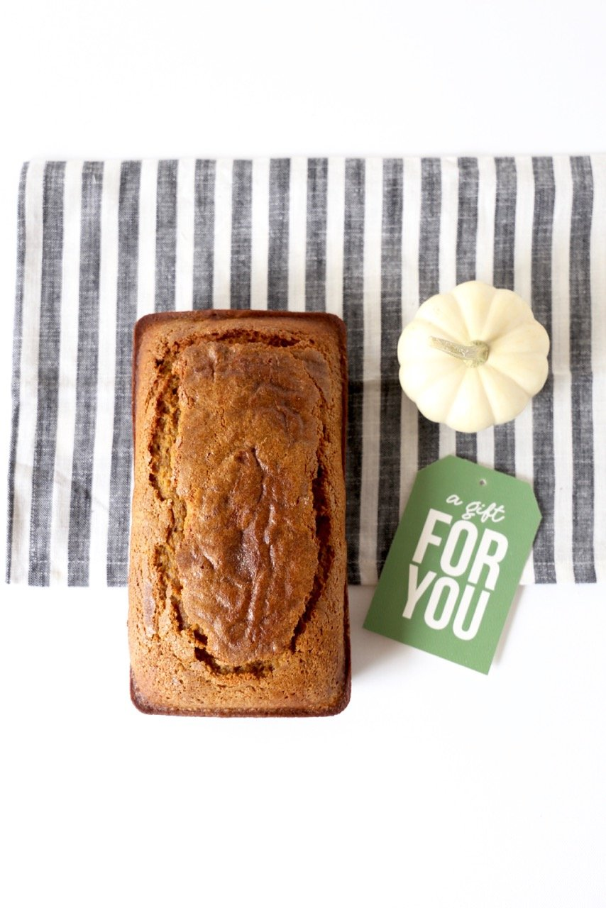 """A loaf of cinnamon sugar pumpkin bread sitting beside a tag that reads """"a gift for you"""""""