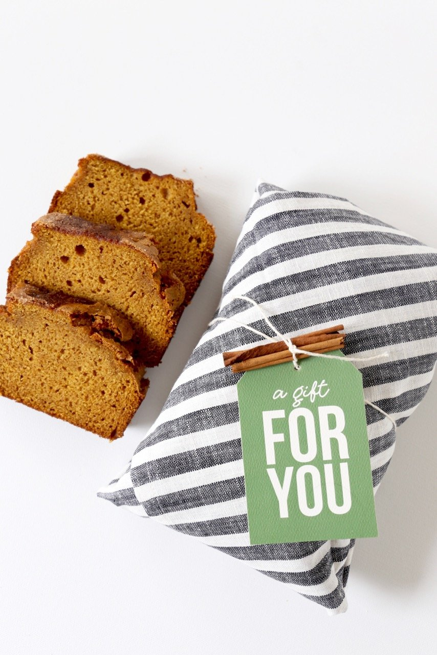 """3 slices of cinnamon sugar pumpkin bread laid next to cinnamon sticks and a tag that reads """"a gift for you"""""""