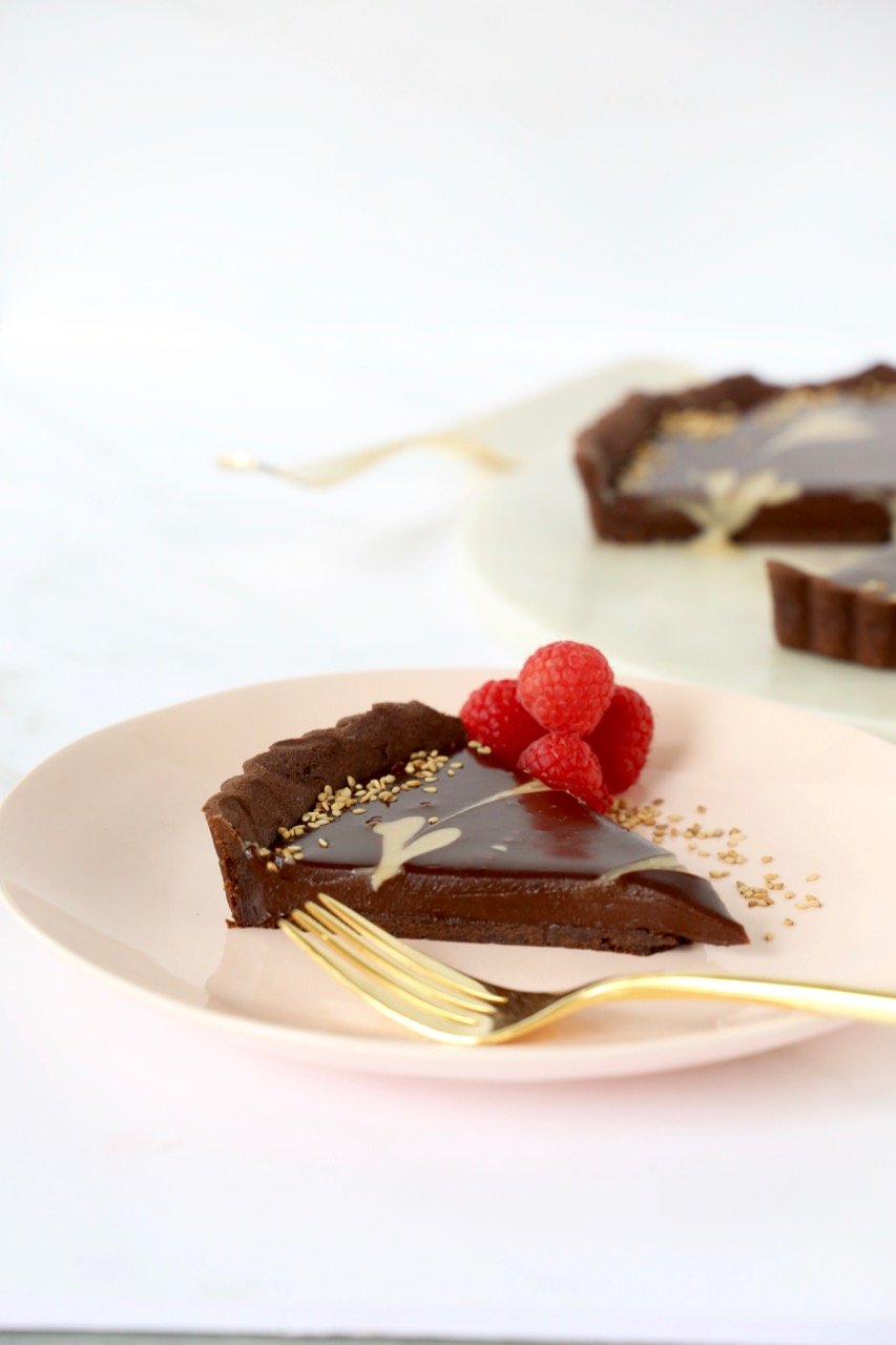 a slice of a chocolate tart filled with chocolate ganache and raspberries on the side