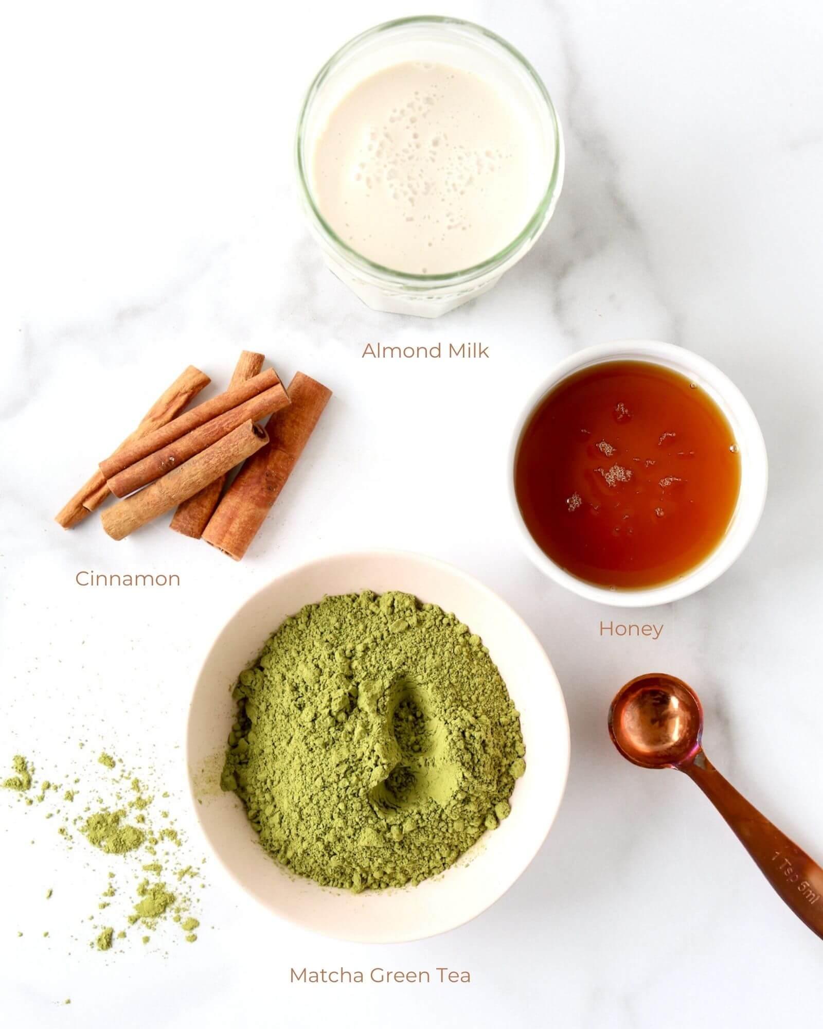 a bowl of matcha tea, a bowl of honey, cinnamon sticks and a jar of almond milk