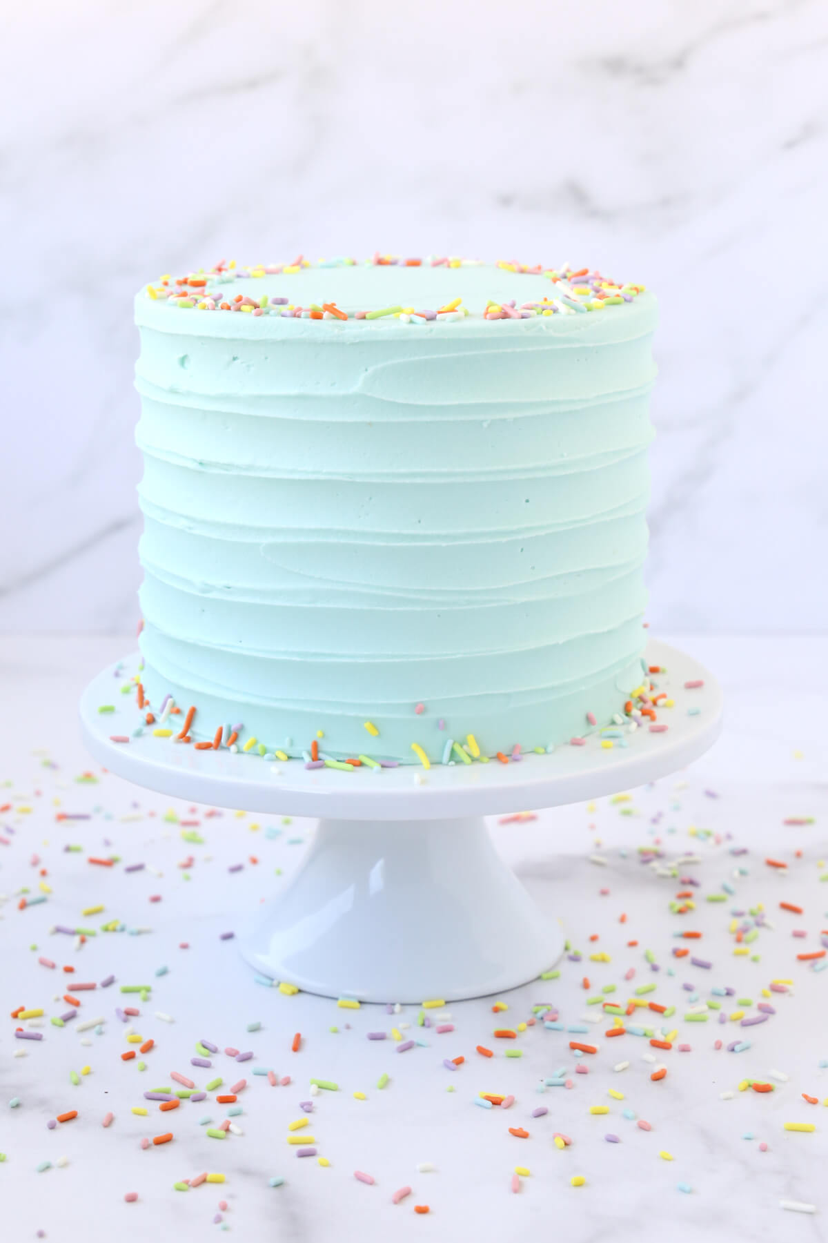 a turquoise frosted cake on a white cake stand surrounded by sprinkles