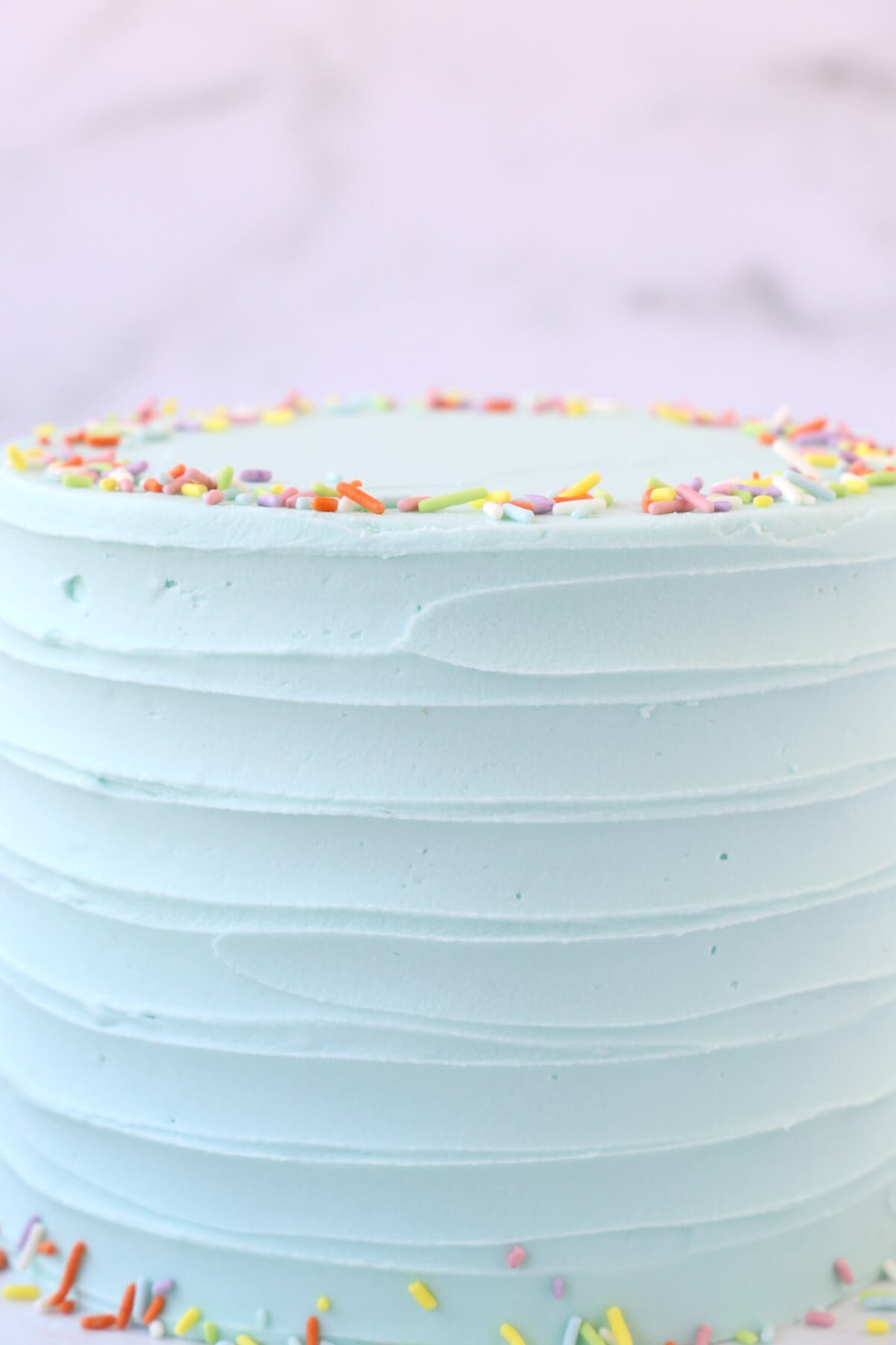 a close up of a cake with light turquoise frosting and rainbow sprinkles