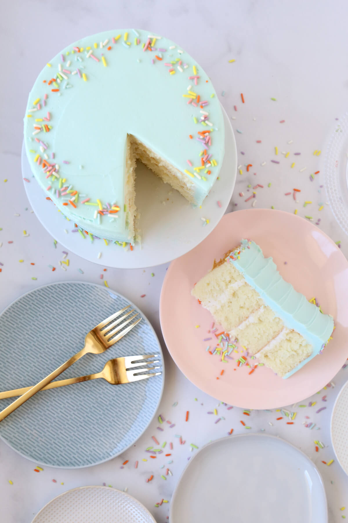 a cake with a slice cut out of it and placed on a pink plate sitting next to two forks.