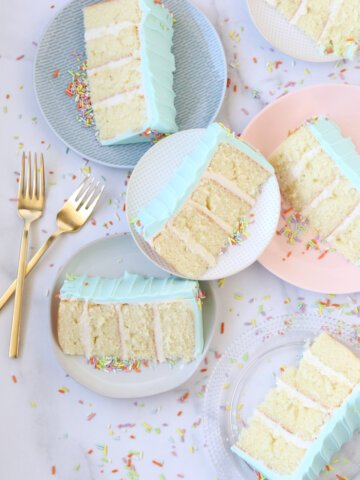 six slices of cake on different plates surrounded by rainbow sprinkles and two gold forks