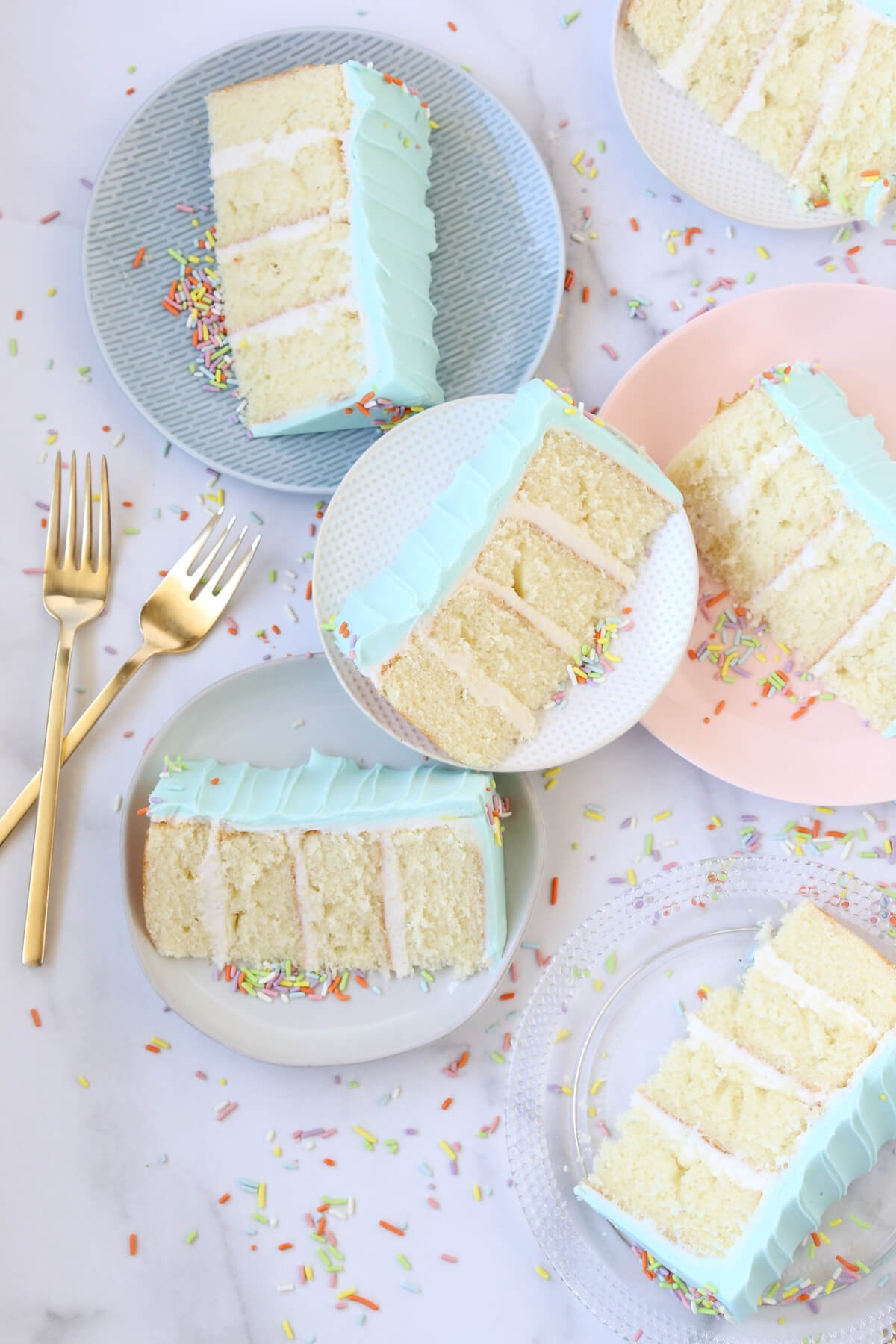 five dessert plates with slices of cake on each, surrounded by sprinkles and two gold forks.