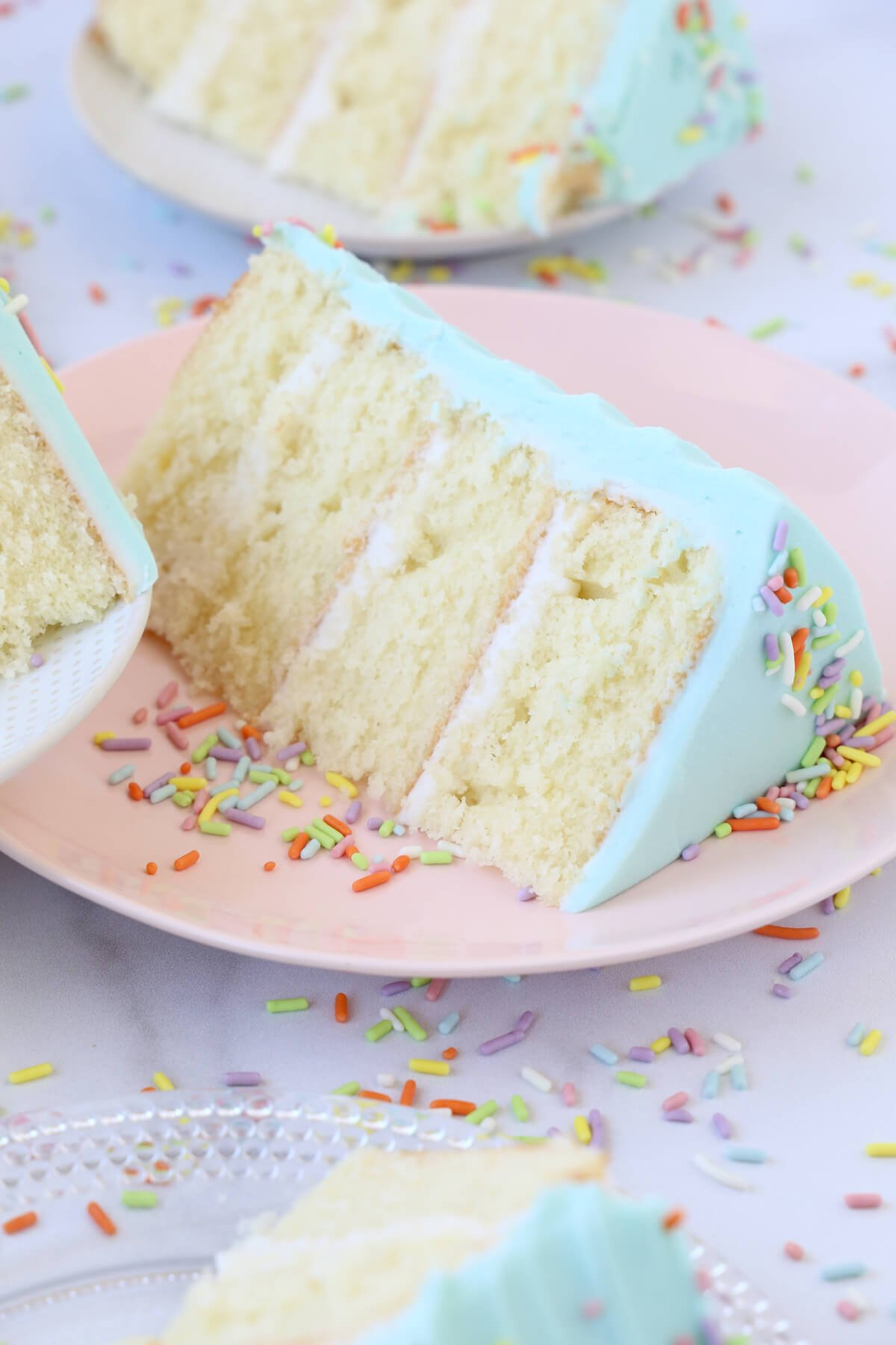 a slice of vanilla cake on a pink plate with rainbow sprinkles