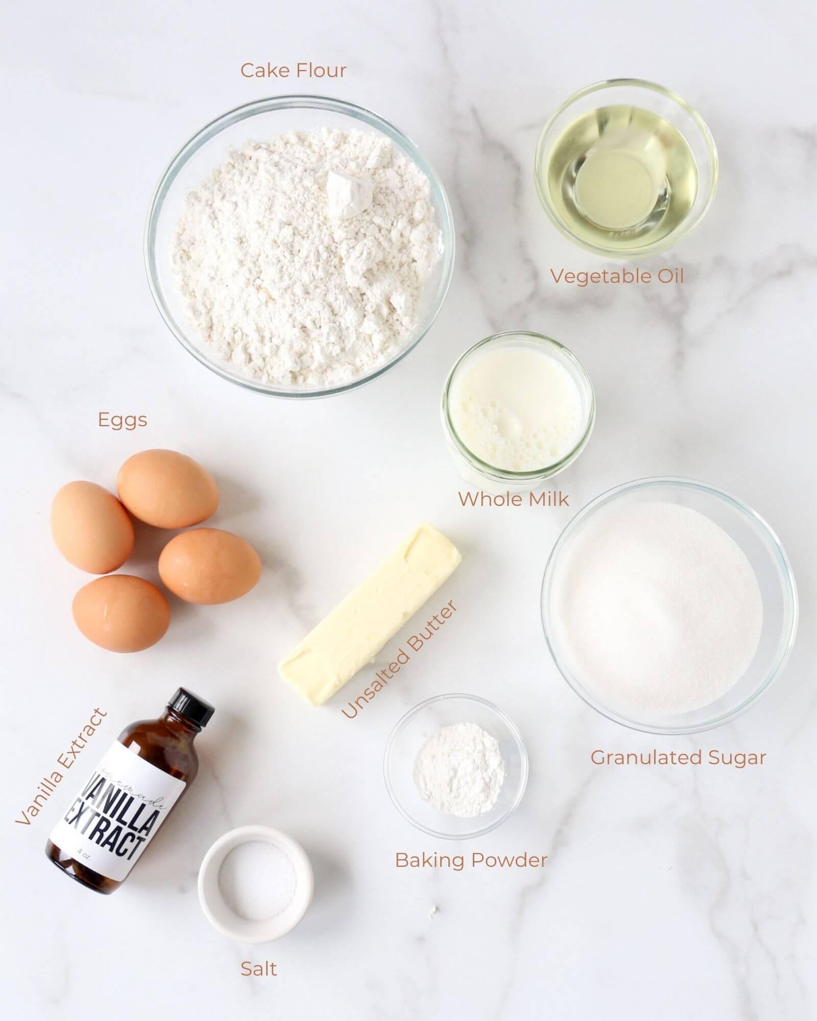 small bowls of flour, oil, milk, sugar, baking powder, salt, eggs and butter.