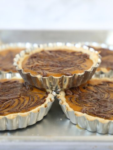 Pumpkin Nutella Swirl Tarts in metal tart molds on a stacked on a sheet pan