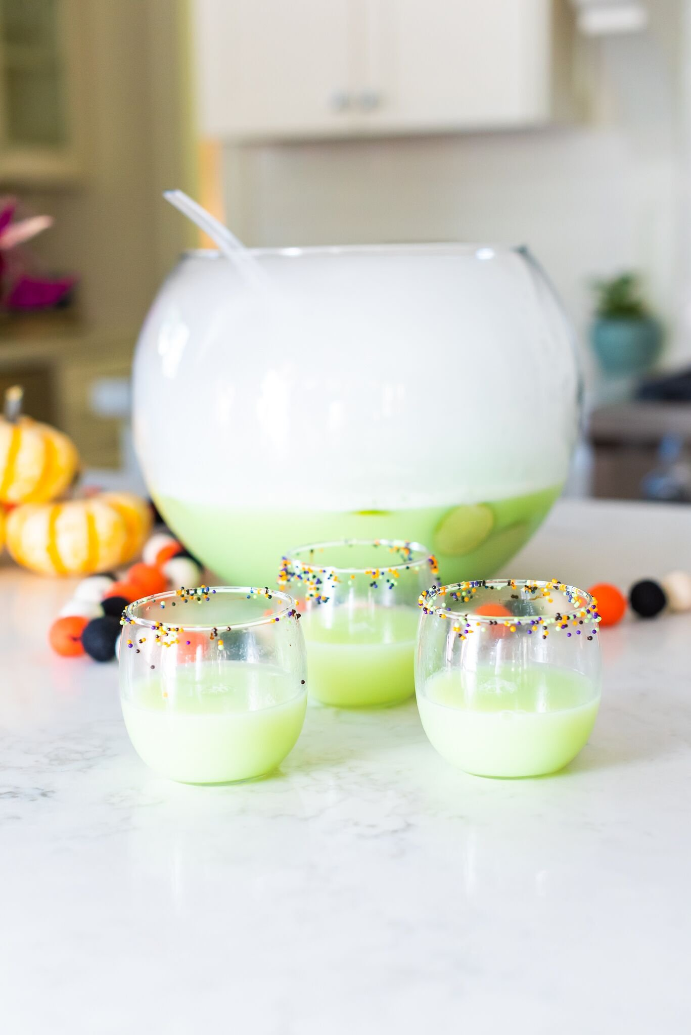 3 glasses full of green punch sitting in front of a large punch bowl