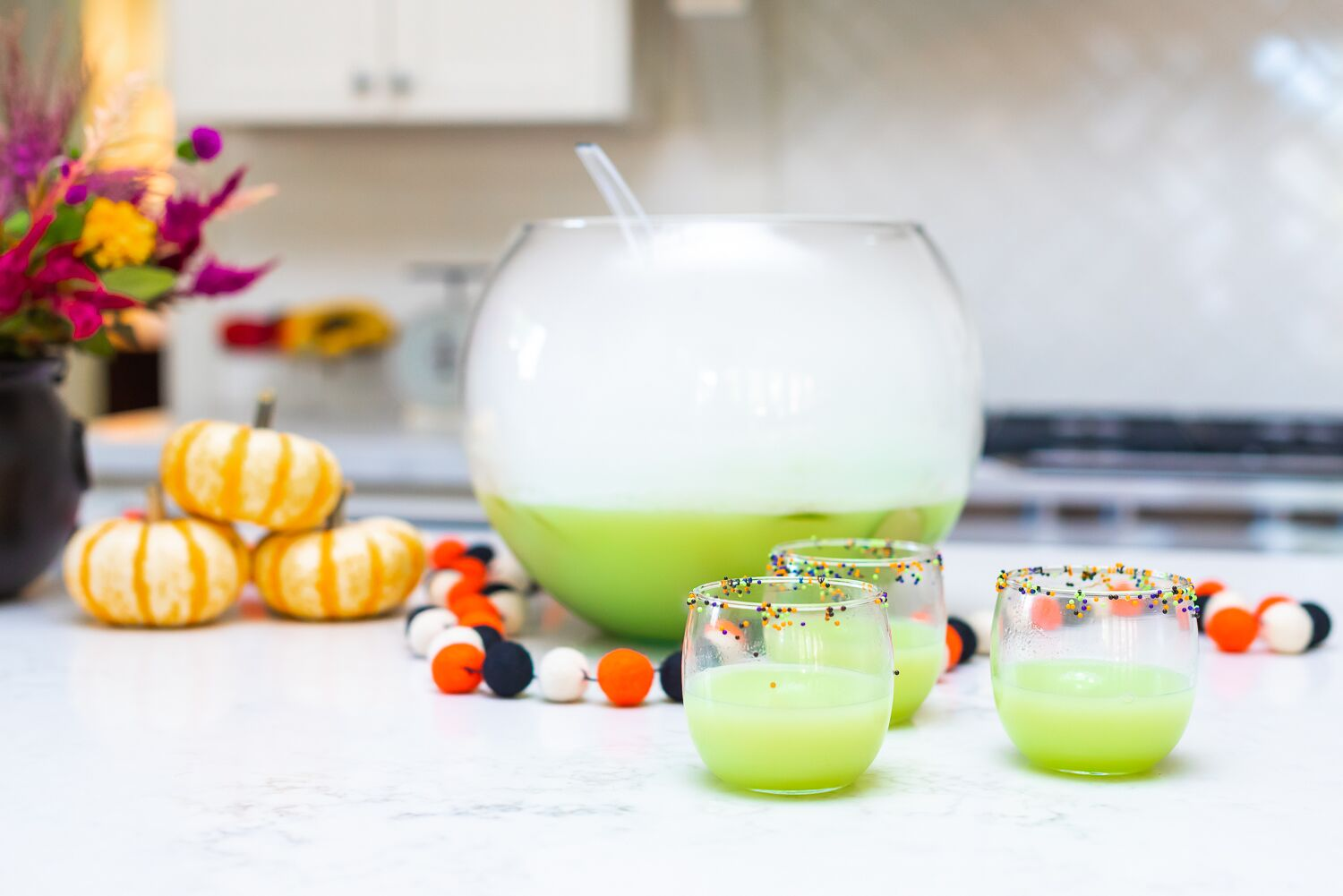 A large punch bowl full of green Hocus Pocus punch, with glasses of punch sitting in front