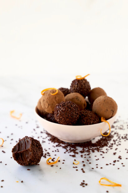 a bowl of chocolate orange truffles and one with a bite out