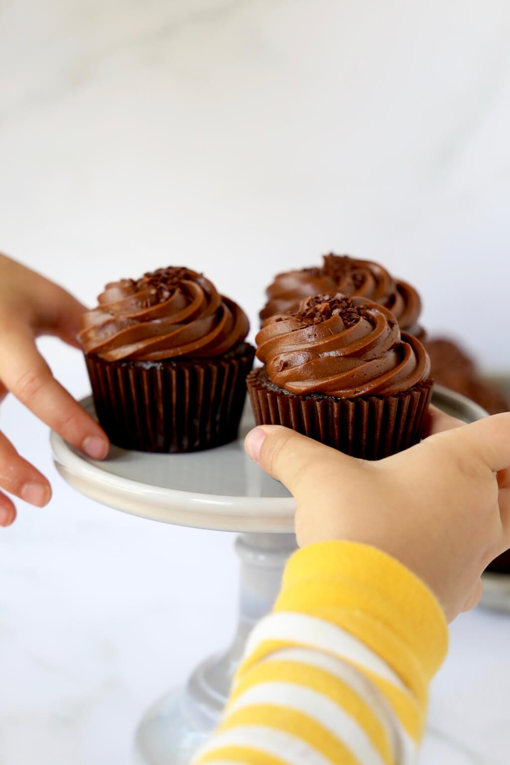 two hands reaching in for a cupcake