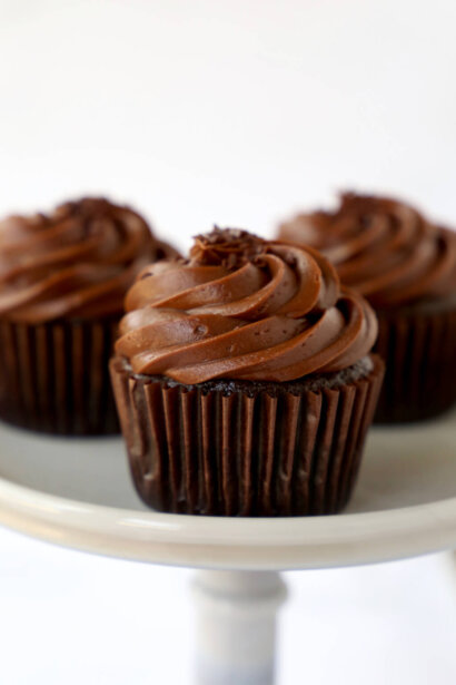Three Chocolate Fudge Cupcakes on a cake stand