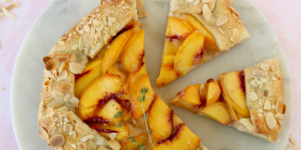 two slices cut out of a peach almond galette