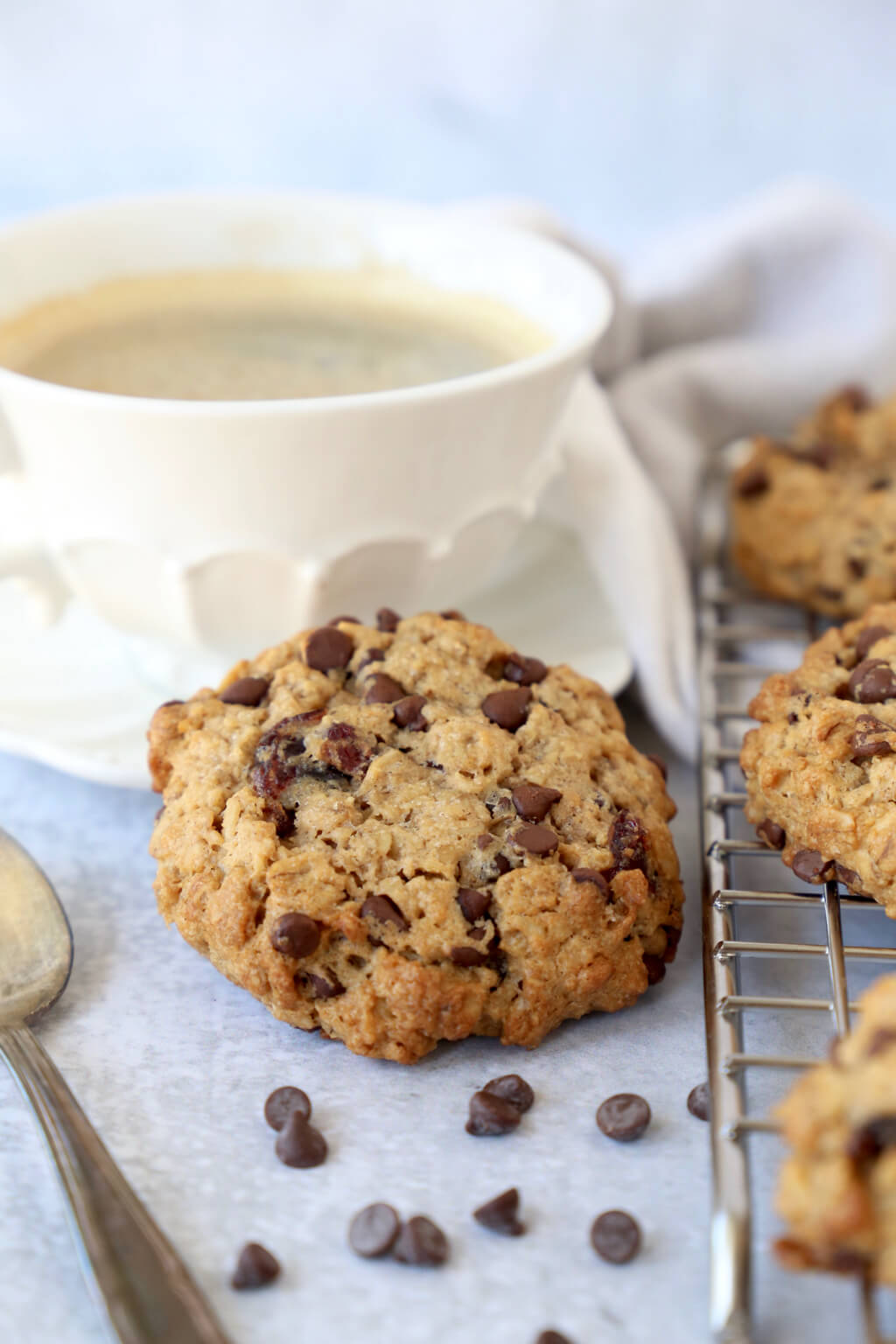 one breakfast cookie resting on the edge of a coffee cup