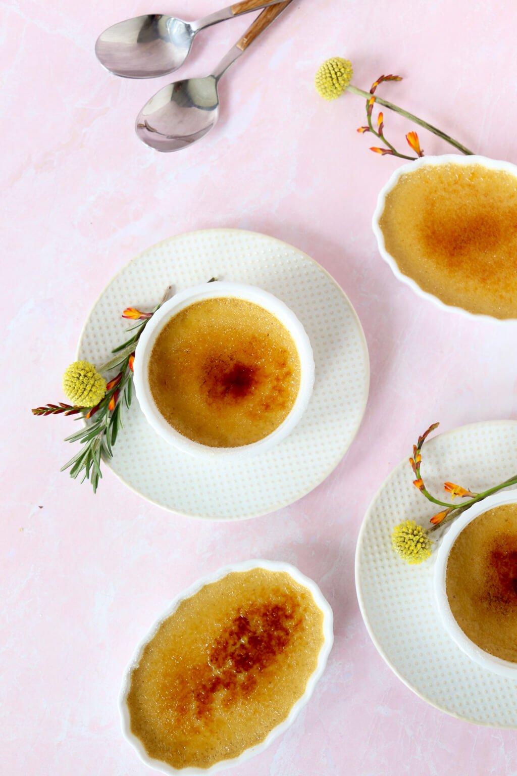 four ramekins of creme brûlée and two spoons