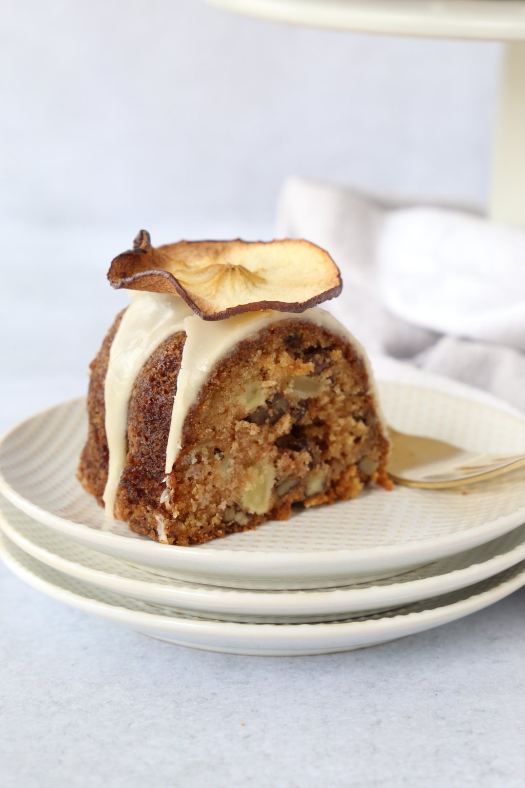 slice of apple spice bundt cake placed on a stack of plates