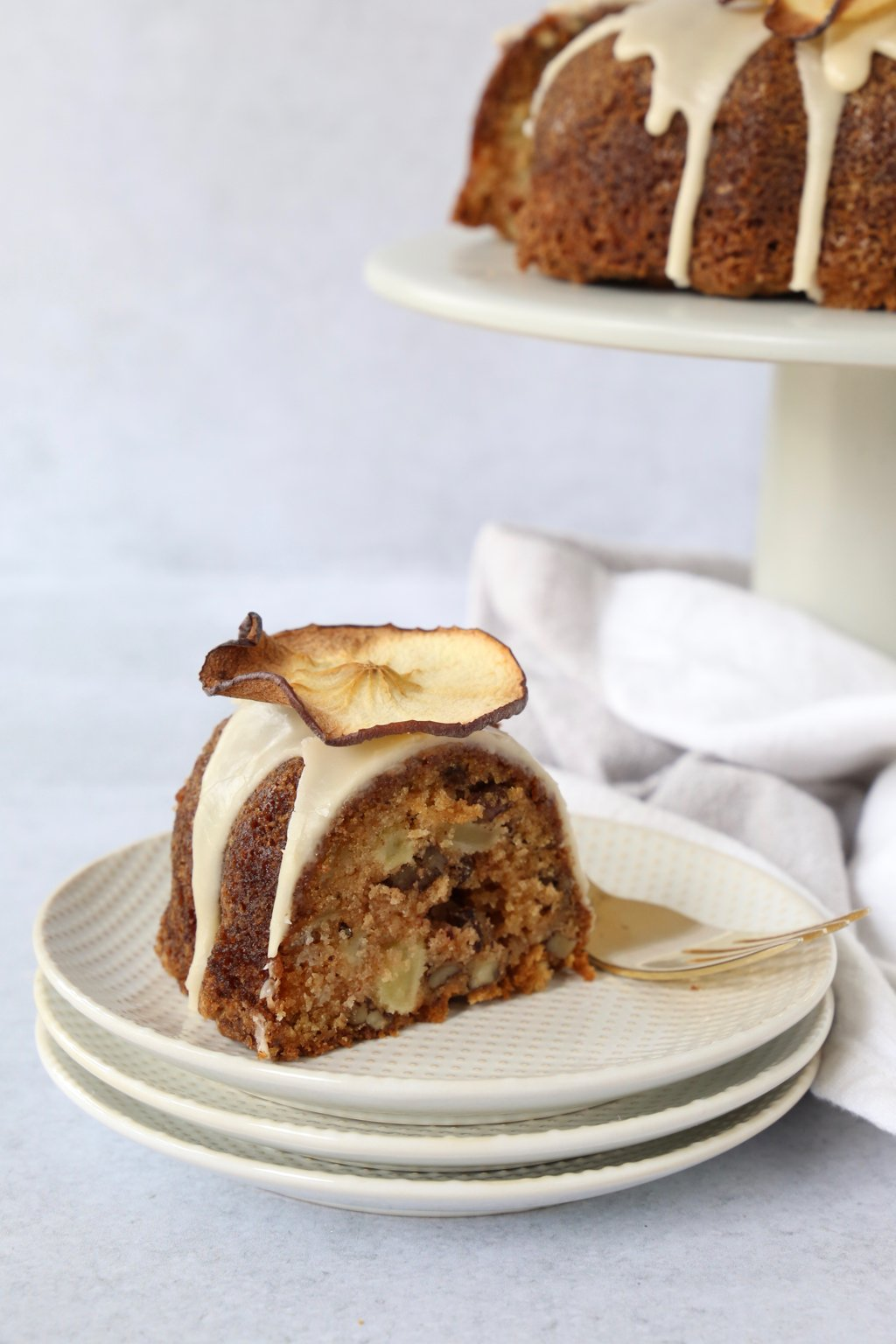 a slice of apple spice bundt cake on a stack of plates with the large bundt cake in the background