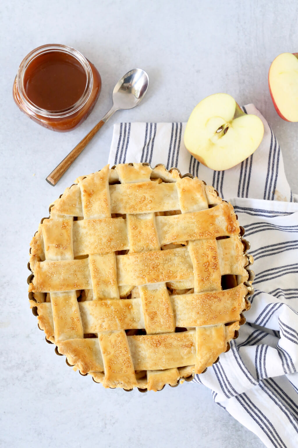 deep dish apple pie with caramel sauce and sliced apples