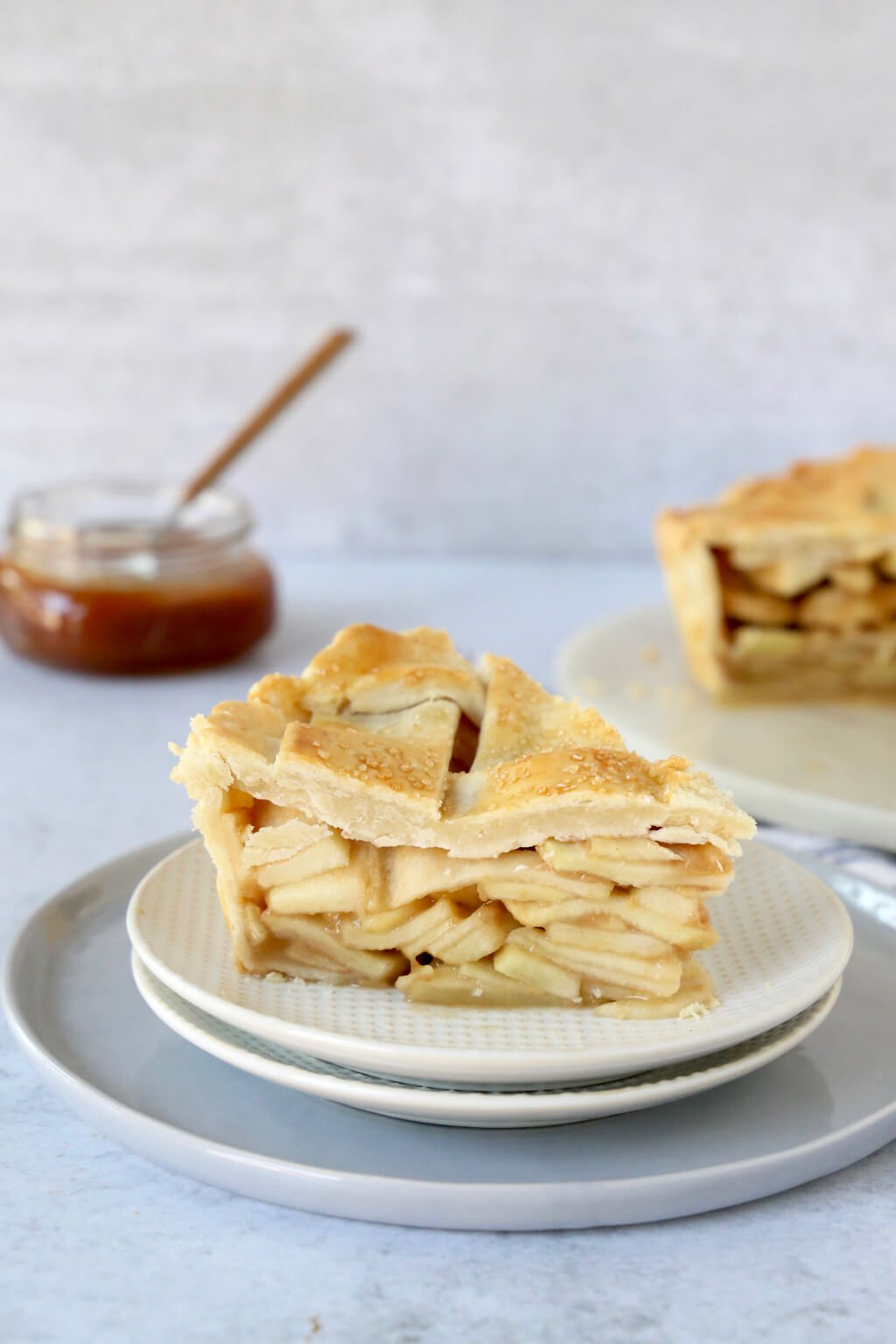 Slice of deep dish apple pie with caramel sauce in the background