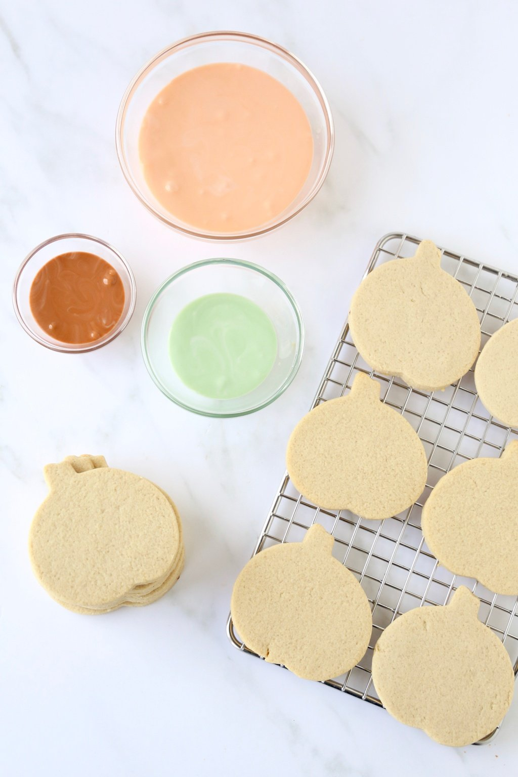 pumpkin shortbread cookies on a cooling rack with three bowls of icing
