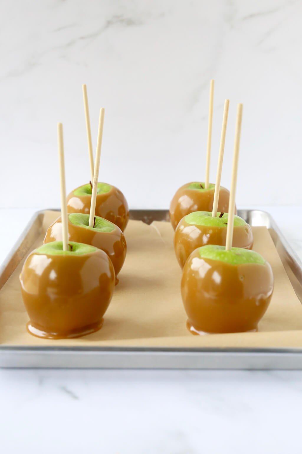 6 caramel apples sitting on a tray
