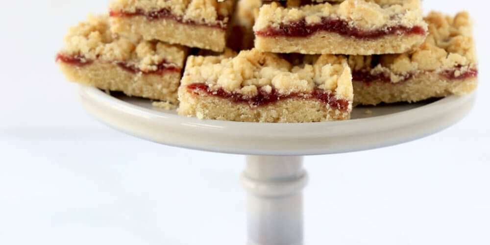 a cake stand of jam shortbread bars