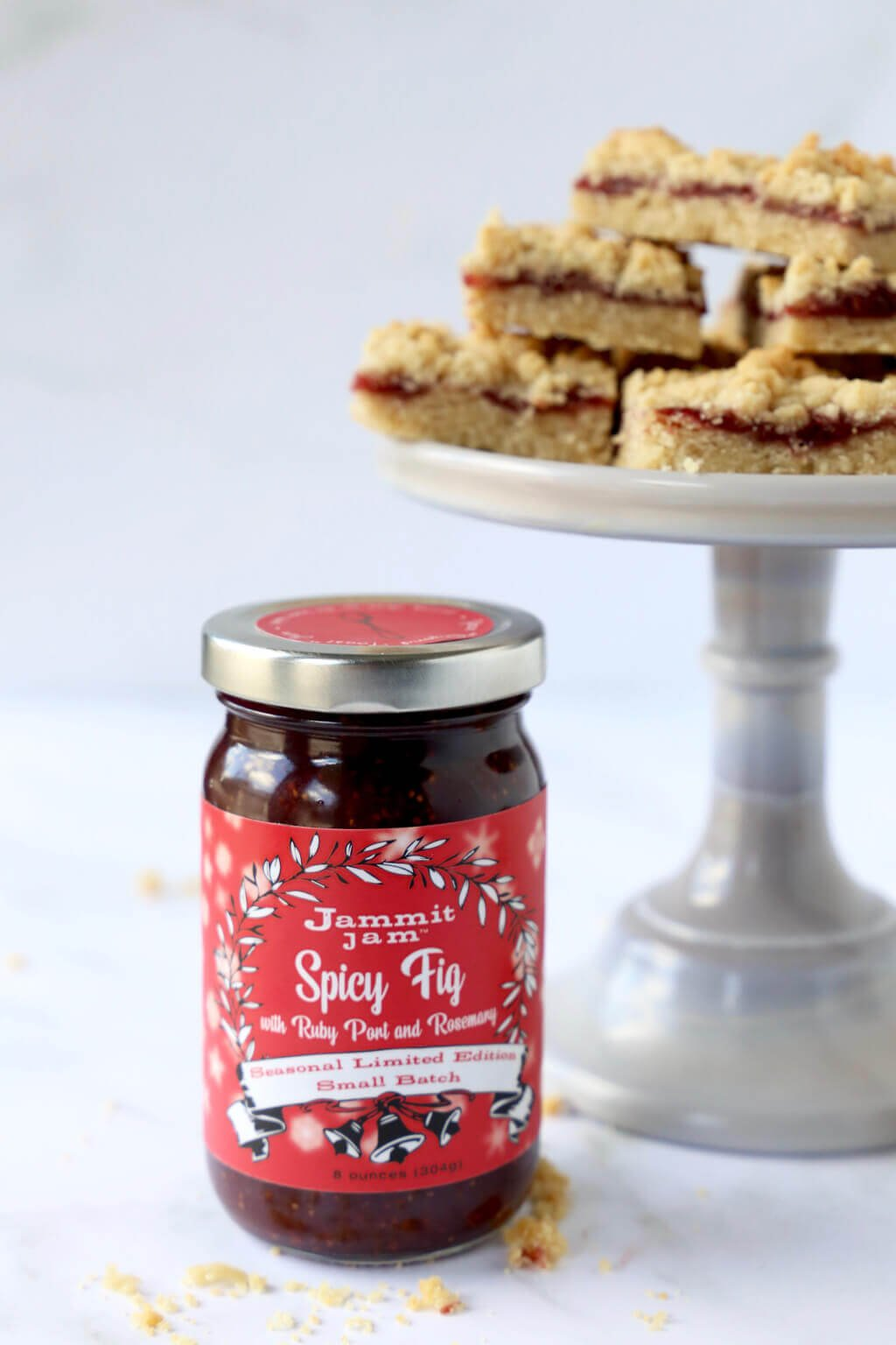 a jar of jammit jam next to a cake stand with a stack of jam shortbread bars