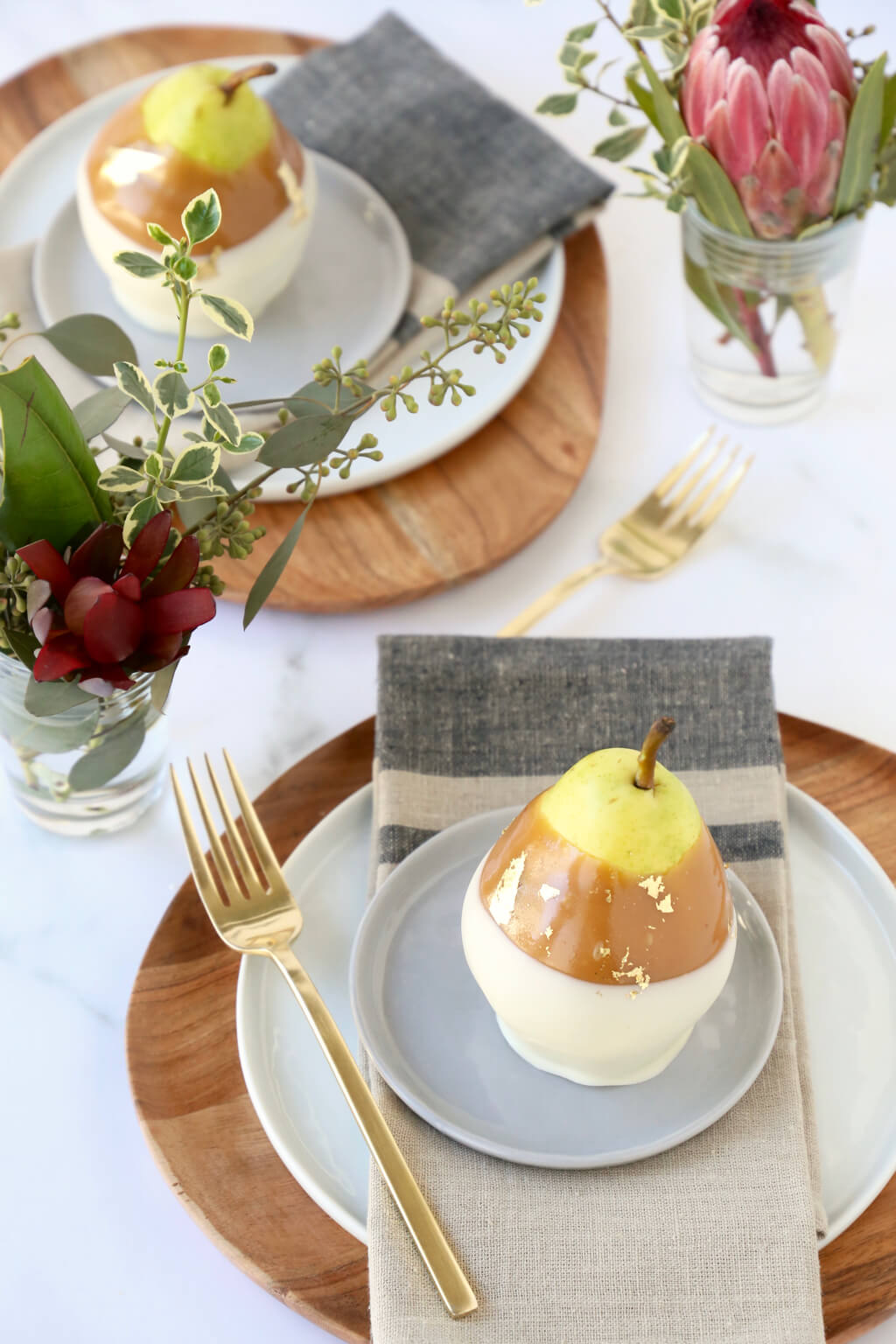 a table set with plates, napkins, forks, flowers and caramel pears
