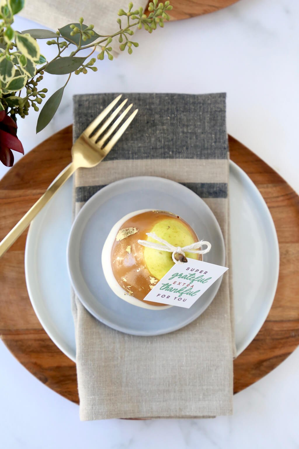 an overhead shot of the caramel pears on a place setting including a place, napkin and fork