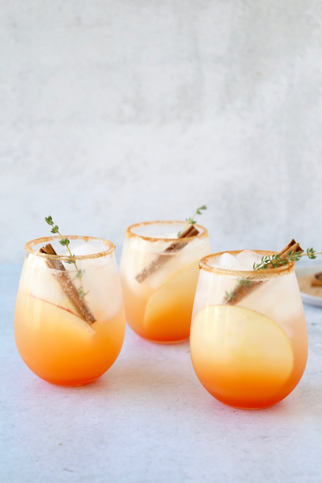 three glasses of a red orange colored cocktail with a cinnamon stick and thyme leave in each glass