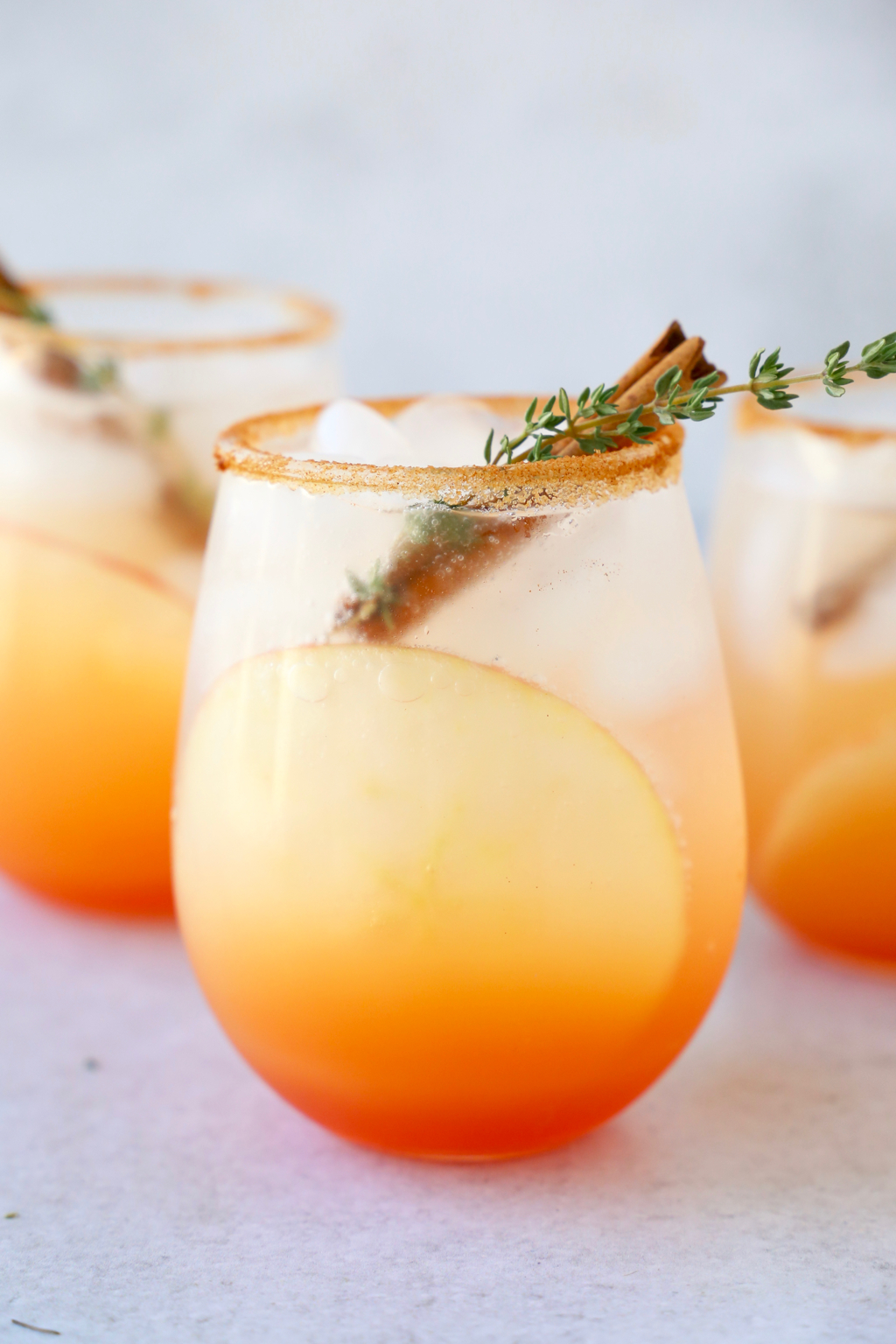 a close up of three glasses of a red orange colored cocktail with a cinnamon stick and thyme leave in each glass