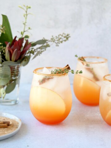 three glasses of a red orange colored cocktail with a cinnamon stick and thyme leave