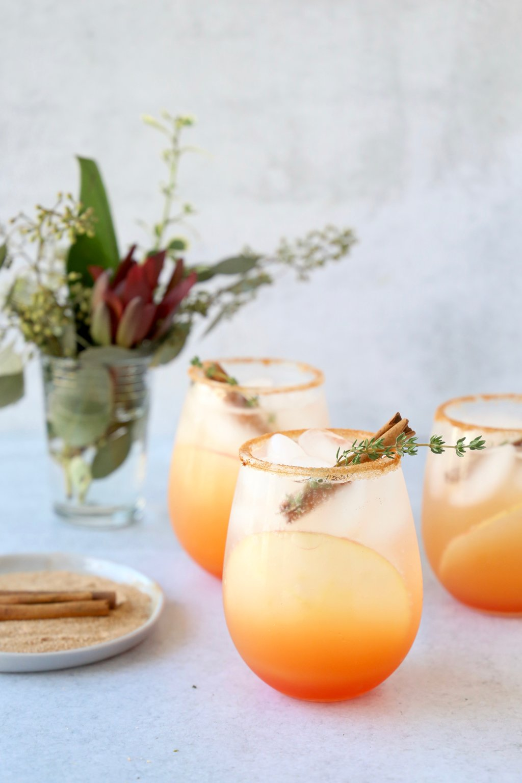 three glasses filled with an orange/red cocktail with a cinnamon stick and thyme leaf sitting next to a small floral arrangement and a dish with cinnamon sugar