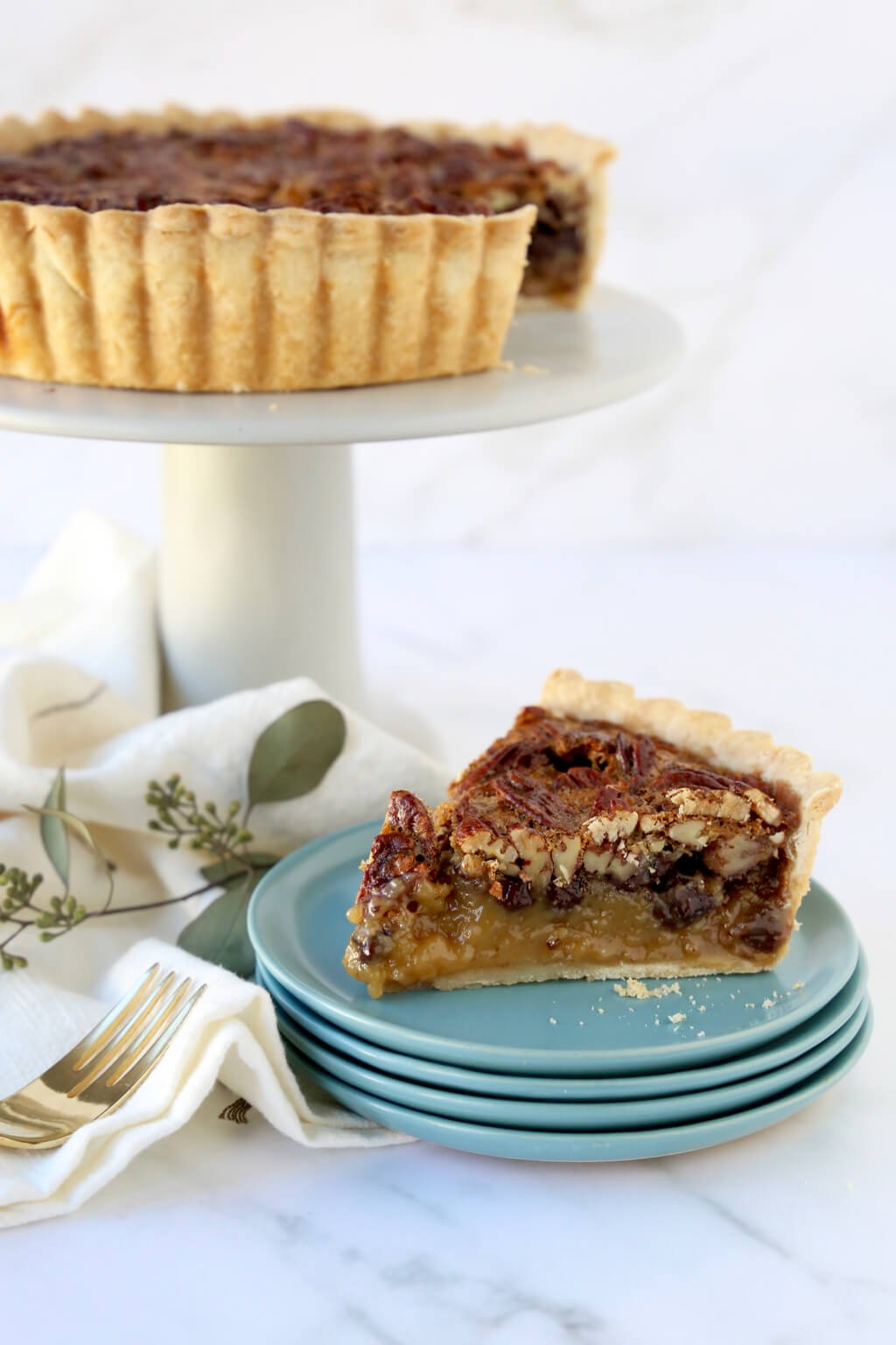 a slice of pecan tart on a stack of dishes and the full tart behind it